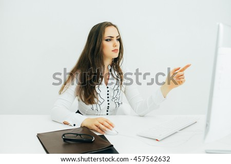 Young woman working in office, sitting at desk, using computer and pointed on monitor - stock photo