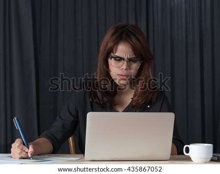 Young woman working in office, sitting at desk, using laptop, smiling  - stock photo