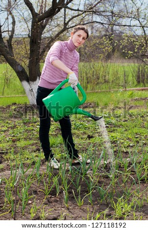 Young woman working in the garden. Horticulture. Watering