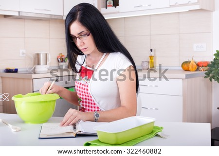 Young woman working in the kitchen, reading recipe for baking