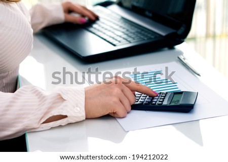 Young woman working in the office. Accounting work. - stock photo