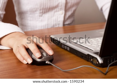 Young woman working on a laptop, close-up on the hand and mouse