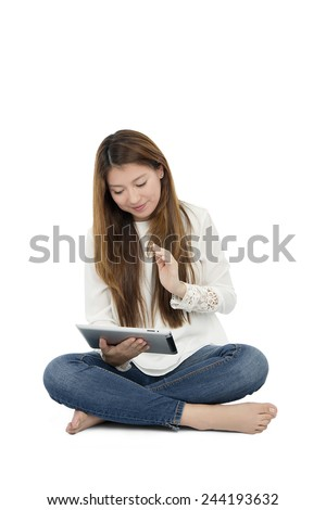 Young woman working on her digital tablet while sitting on the floor - stock photo
