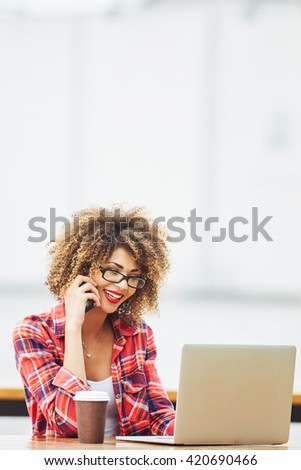 Young woman working on laptop and talking on mobile phone  - stock photo