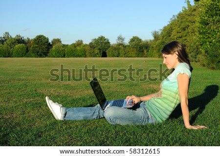 Young woman working on notebook outdoor. - stock photo