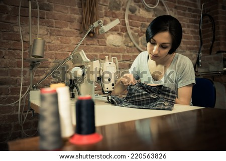 Young woman working on sewing machine - stock photo
