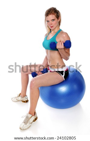 Young woman working out while sitting on a fitness ball - stock photo