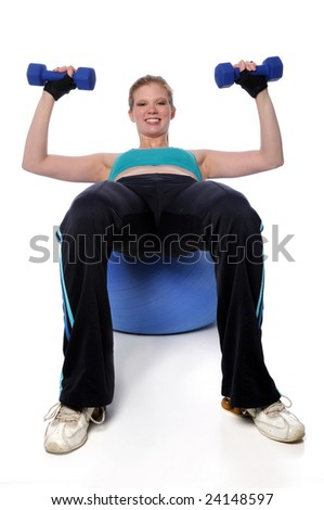 Young Woman Working out with dumbbells on a fitness ball - stock photo