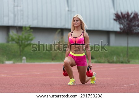 Young Woman Working Out With Kettle Bell Exercise Outdoor