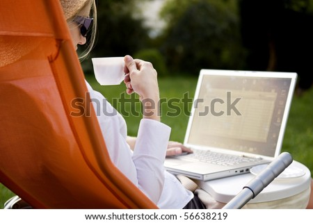 young woman working outside on computer and drinking coffee - stock photo