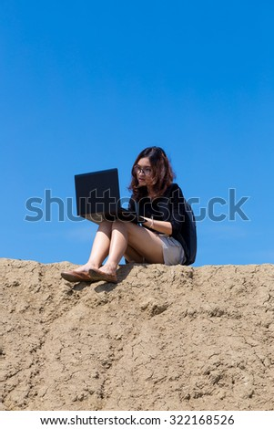 young woman working with laptop on the mountain with blue sky background