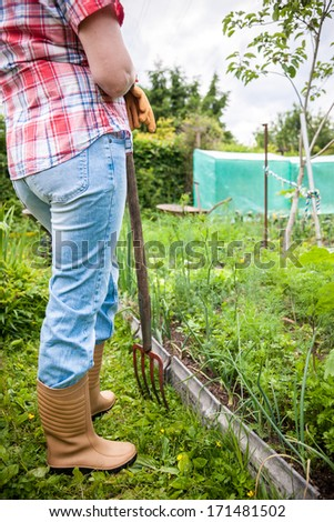 Young woman working with spade fork in the garden - stock photo