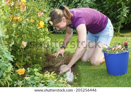 Young woman works in the garden - stock photo