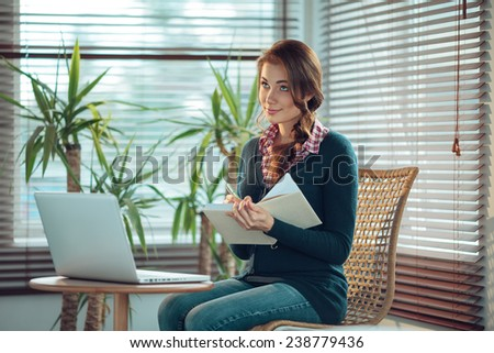 Young woman writing in a notebook with a blank cover - stock photo