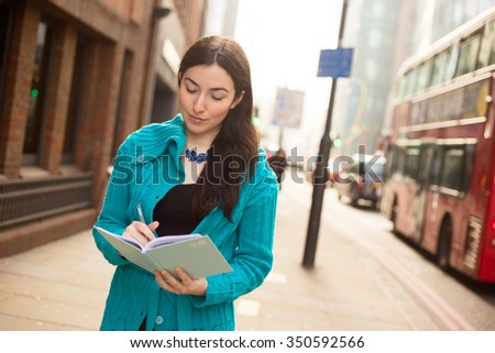 young woman writing in a textbook in the street