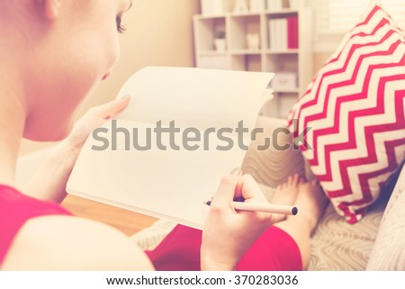 Young woman writing in her notebook on at home on her couch - stock photo