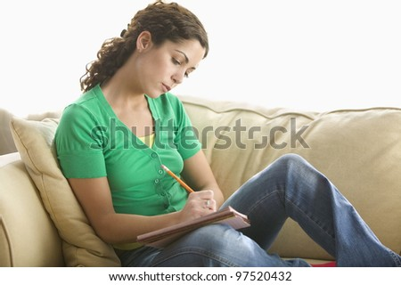 Young woman writing in notepad - stock photo