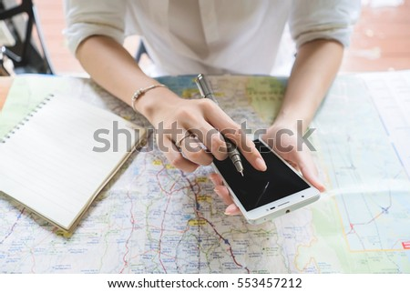 Young woman writing in the note book while using smartphone,Map travel trip destination direction planning concept.