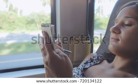 Young woman writing lecture on bus while traveling.