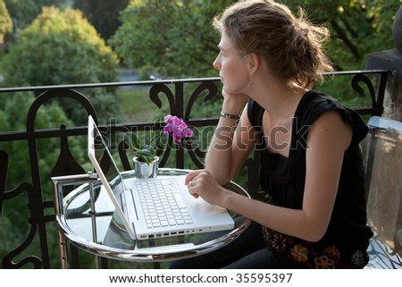 young woman writing on a white modern laptop computer on a balcony in art nouveau - stock photo