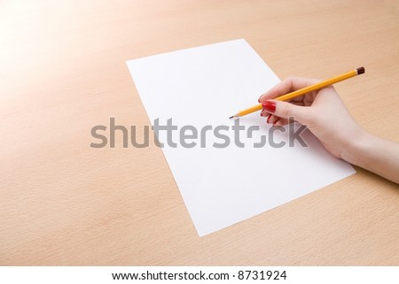 Young woman writing on a white sheet of paper.