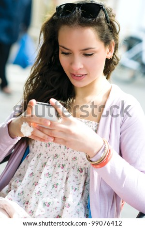 Young woman writing on mobile phone in a street cafe - stock photo