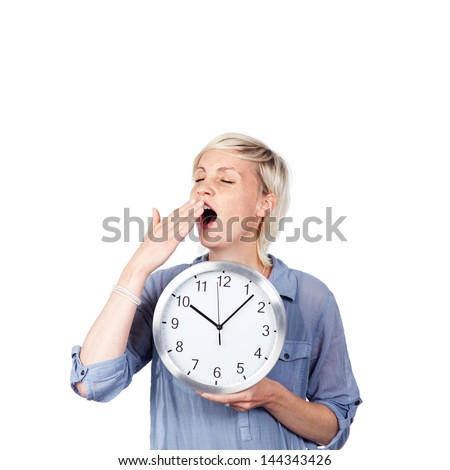 Young woman yawning with closed eyes as she holds a clock against white background - stock photo