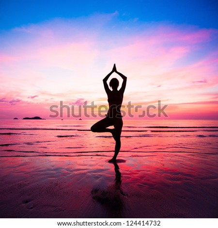 Young woman yoga practice at the seaside at sunset - stock photo