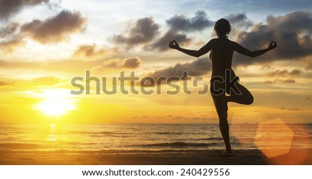 Young woman yoga silhouette meditating on the ocean beach at amazing sunset. - stock photo