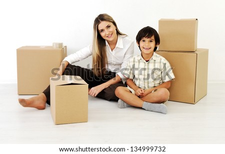 Young women and little boy  playing with cardboard box - stock photo