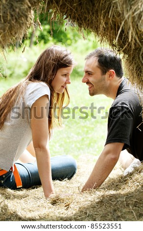 Young women and man  in haystack - stock photo