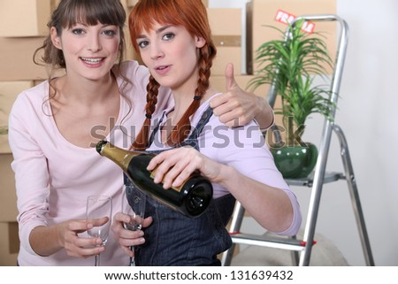 Young women celebrating on moving day - stock photo
