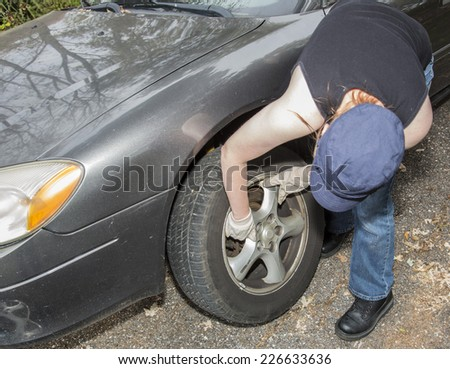 Young women changing tire on side of the road - stock photo