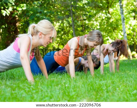Young women doing push-ups in nature. - stock photo