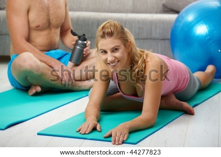 Young women doing streching exercise lying on fitness mat.