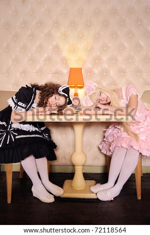 Young women dressed as dolls, sleeping at a table in the doll house. - stock photo