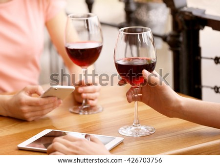 Young women drinking wine in cafe