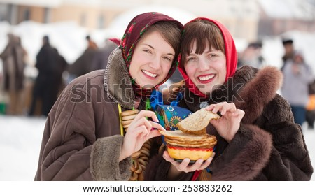 Young women eating pancake during  Pancake Week outdoor - stock photo