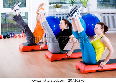 Young women exercising in a step aerobics class - stock photo