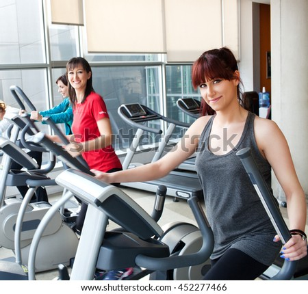 Young women exercising on cross trainer machines