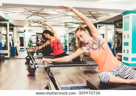 Young women exercising on pilates reformers beds. Focus is on the background. - stock photo