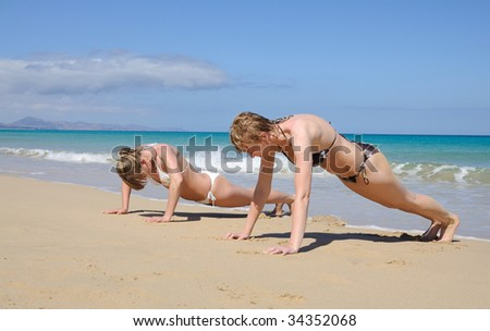 Young women exercising on the beach - stock photo