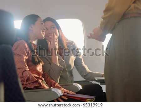 Young women giggling about young man - stock photo