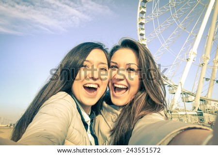 Young women girlfriends taking a selfie at luna park with ferris wheel - Concept of friendship and fun with new trends and technology - Best female friends catching the moment with modern smartphone - stock photo