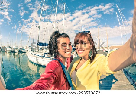 Young women girlfriends taking selfie with sailboats - Friendship concept with new trends and technology - Best female friends catching the moment with modern smartphone - Soft vintage filtered look  - stock photo