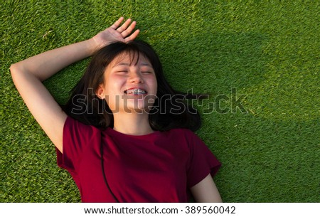 Young women happy lying on grass green