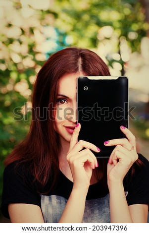 Young women hide her face by modern tablet computer and smiling wide, instagram color filter - stock photo