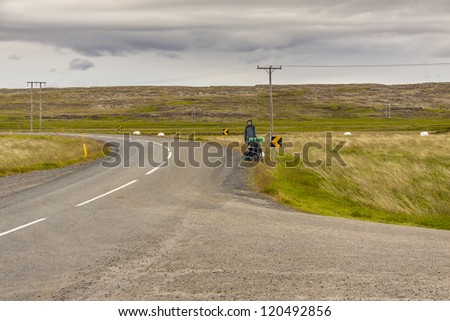 Young women hitchhiking on Iceland. Summer windy day.