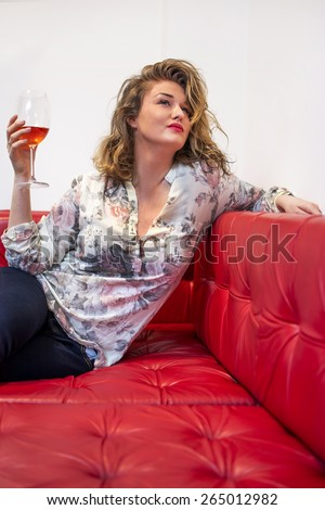 Young women holding glass of red wine and sitting on sofa. - stock photo