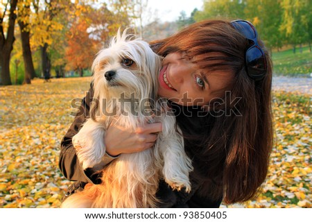 Young women holding her lhasa apso puppy after playing in the park - stock photo